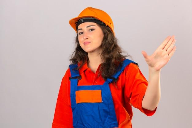 Młoda kobieta konstruktora w mundurze budowy i hełmie ochronnym uśmiechnięty macha ręką gest powitania i pozdrowienia na izolowanej białej ścianie