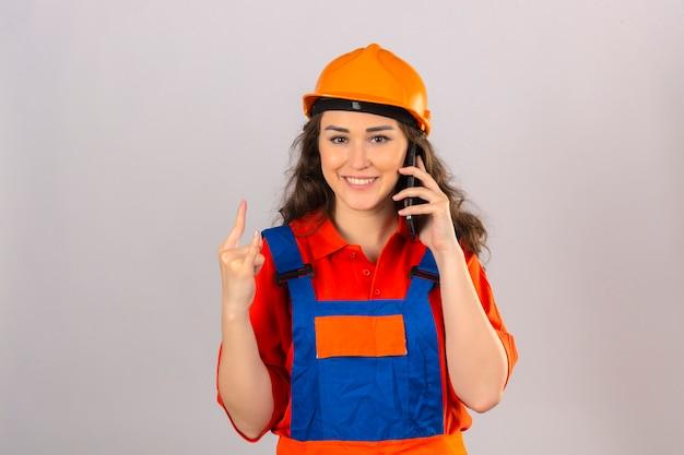 Młoda kobieta konstruktora w mundurze budowy i hełmie ochronnym z uśmiechem rozmawia przez telefon komórkowy i robi znak rocka palcami na izolowanych białej ścianie