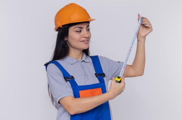 Młoda kobieta konstruktora w mundurze budowy i kasku ochronnym gospodarstwa miara taśmy patrząc na to uśmiechnięty stojący nad białą ścianą