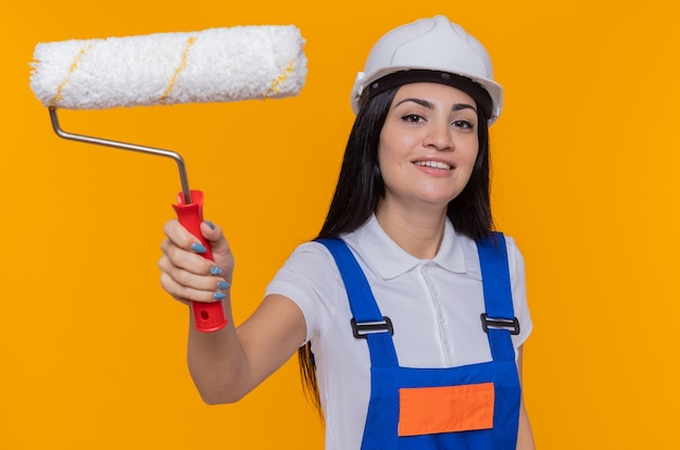 Młoda kobieta konstruktora w mundurze konstrukcyjnym i hełmie ochronnym, trzymając wałek do malowania patrząc na przód uśmiechnięty pewny siebie stojący nad pomarańczową ścianą