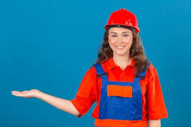 Młoda kobieta konstruktora w mundurze konstrukcyjnym i hełmie ochronnym uśmiechnięty wesoły, prezentując i wskazując dłonią patrząc w kamerę na odosobnionej niebieskiej ścianie