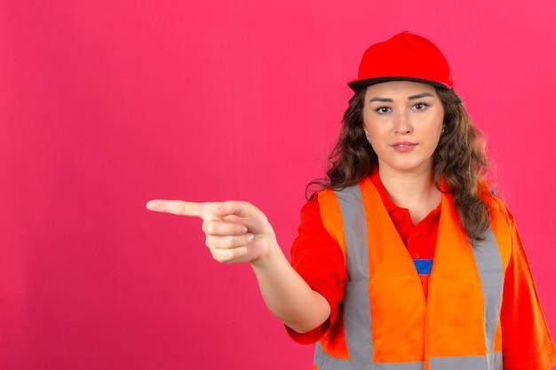 Młoda kobieta konstruktora w mundurze konstrukcyjnym i hełmie ochronnym, wskazując palcem w bok nad izolowaną różową ścianą