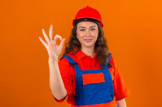 Młoda kobieta konstruktora w mundurze konstrukcyjnym i kasku ochronnym, patrząc pewnie, uśmiechając się radośnie, robi znak ok na odizolowanej pomarańczowej ścianie