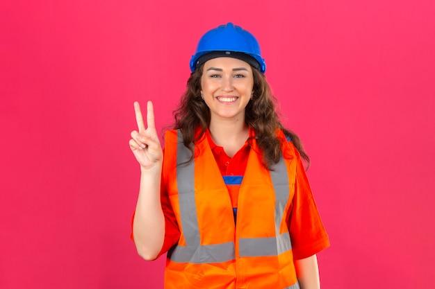 Młoda kobieta konstruktora w mundurze konstrukcyjnym i kasku ochronnym, uśmiechając się wesoło i czyniąc znak zwycięstwa na izolowanej różowej ścianie