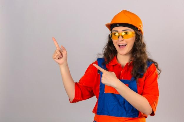 Młoda kobieta konstruktora w mundurze konstrukcyjnym i kasku ochronnym, wskazując palcami na bok z radosną i zabawną twarzą na odizolowanej białej ścianie