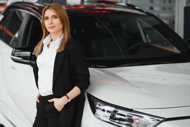 Młoda kobieta konsultant w salonie stojącym w pobliżu samochodu