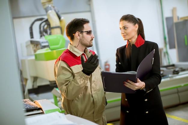 Młoda kobieta kontroluje proces w fabryce z męskim pracownikiem