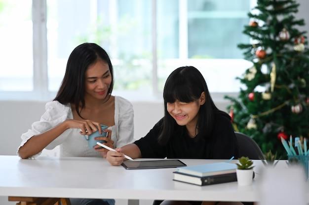 Młoda kobieta korepetytor i student robi lekcję online z cyfrowym tabletem w domu. koncepcja edukacji online.