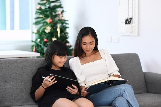 Młoda kobieta korepetytor pomaga jej uczniowi odrabianiu lekcji w szkole na cyfrowym tablecie. koncepcja edukacji online.