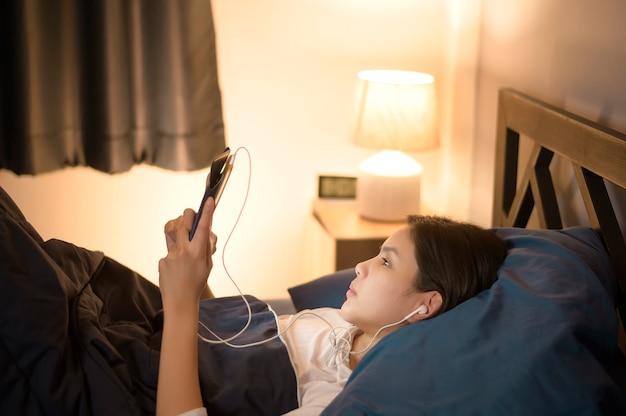Młoda kobieta korzysta z tabletu, ogląda filmy lub rozmawia wideo z przyjaciółmi lub rodziną w swojej sypialni, night light