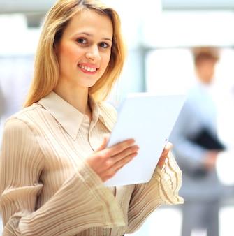 Młoda kobieta korzysta z tabletu w swoim biurze