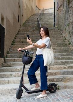 Młoda kobieta korzystająca z ekologicznego skutera