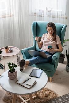 Młoda kobieta korzystająca z laptopa, telefonu komórkowego, picia kawy, wielu urządzeń