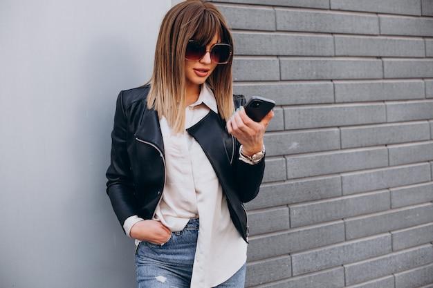 Młoda kobieta korzystająca z telefonu przy centrum handlowym
