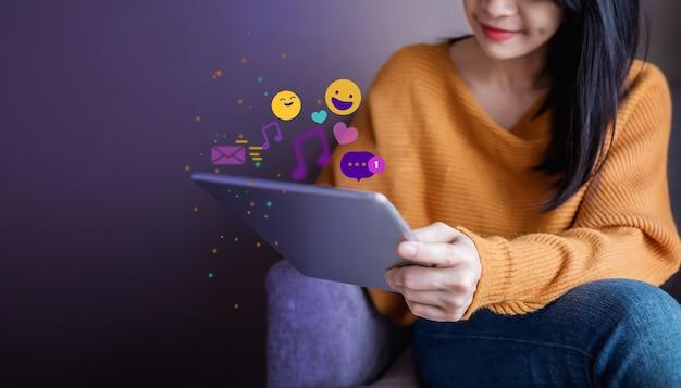 Młoda kobieta korzystających podczas korzystania z aplikacji social media za pośrednictwem cyfrowego tabletu. styl życia współczesnej kobiety. otoczony wieloma ikonami