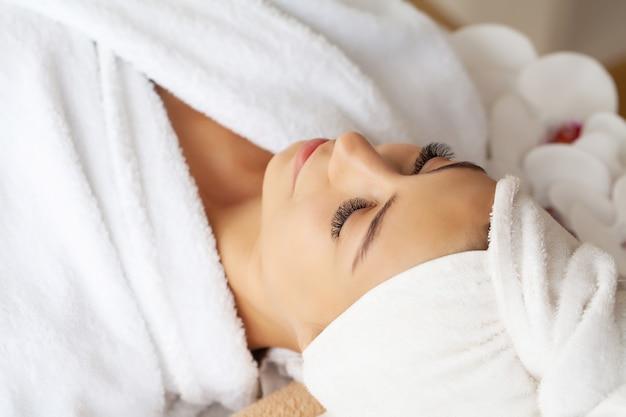 Młoda kobieta korzystających z masażu twarzy w salonie spa.