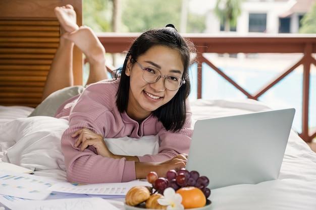 Młoda kobieta korzystała z wideokonferencji na laptopie i jadła owoce na łóżku, pracując z koncepcji domu