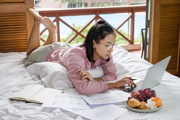 Młoda kobieta korzystała z wideokonferencji na laptopie i jadła owoce na łóżku, zdrowa żywność i pracowała w domu