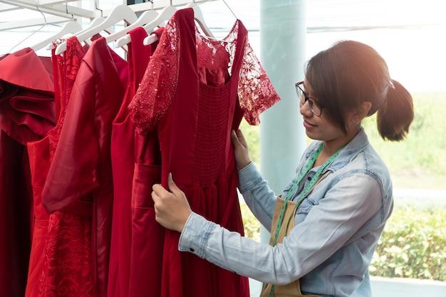 Młoda kobieta krawcowa sprawdza sukienki