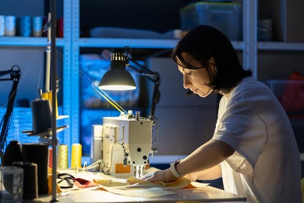Młoda kobieta krawcowa szyć na maszynie do szycia krawiec siedzi w miejscu pracy w atelier warsztatu mody