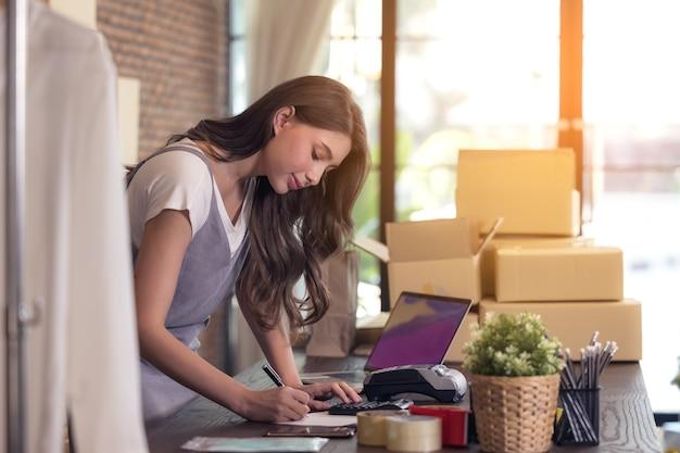Młoda kobieta krawiecka z laptopem odpowiada na e-maile, przedsiębiorczy sukces kobiety biznesu. sprzedaż dostawa paczek online