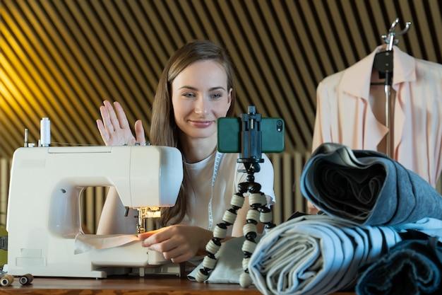 Młoda kobieta kręci lekcję wideo, która szyje na maszynie do szycia, prowadzi blog o szyciu