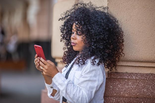 Młoda kobieta kręcone czarne włosy spaceru za pomocą telefonu komórkowego. sms-y na ulicy. duże miasto.