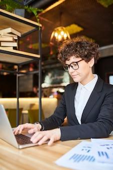 Młoda kobieta kręcone w garnitur i okulary, koncentrując się na sieci, siedząc przed laptopem w kawiarni