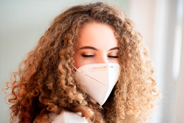 Młoda kobieta kręcone włosy ubrana w maskę medyczną i zamknięte oczy zbliżenie portret twarzy na białym tle na białej powierzchni