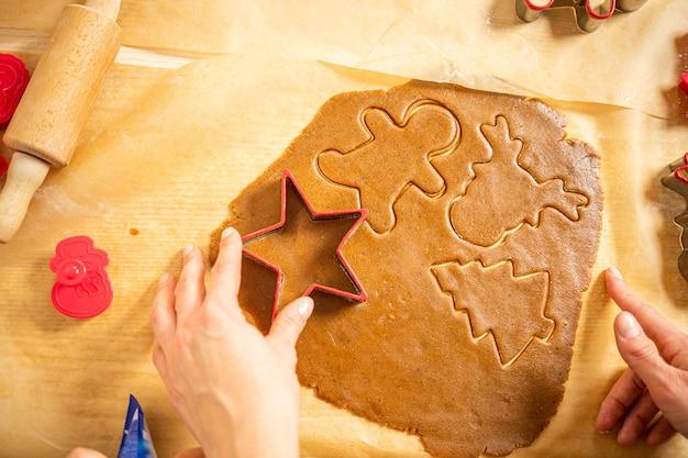 Młoda kobieta krojenia ciasta piernikowego w różne kształty na brązowym papierze do pieczenia. przygotowuję się do świąt.