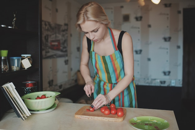 Młoda kobieta krojenie pomidorów