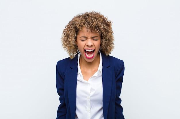 Młoda kobieta krzyczy agresywnie, wygląda na bardzo zła, sfrustrowana, oburzona lub zirytowana, nie krzyczy pod ścianę