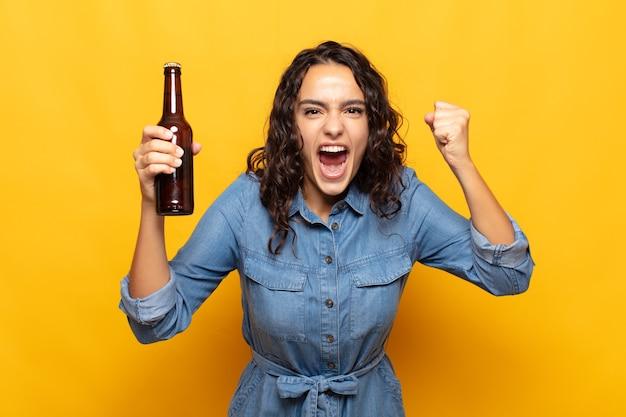 Młoda kobieta krzyczy agresywnie ze złym wyrazem twarzy lub z zaciśniętymi pięściami świętując sukces