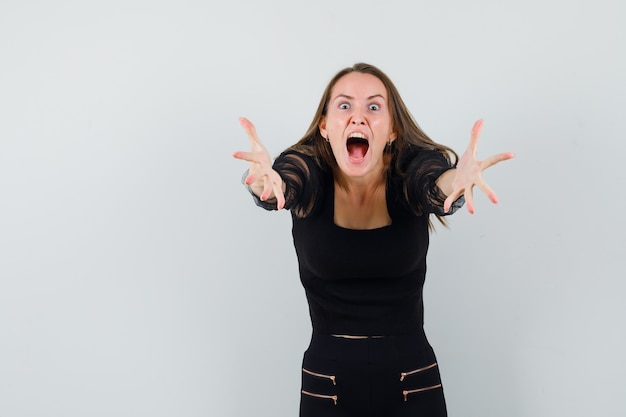 Młoda kobieta krzyczy i trzyma się za ręce, jakby próbowała dostać coś w czarnej bluzce i czarnych spodniach i wyglądała na wściekłą. przedni widok.