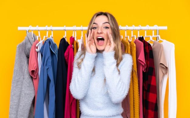Młoda kobieta krzyczy z usta szeroko otwartą w sklepie odzieżowym nad odosobnioną kolor żółty ścianą