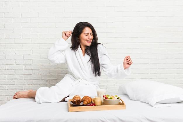 Młoda kobieta krzywego biorąc śniadanie na łóżku, taniec i zabawę