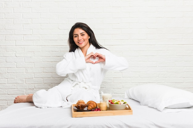 Młoda kobieta krzywego, biorąc śniadanie na łóżku, uśmiechając się i pokazując kształt serca z rąk.
