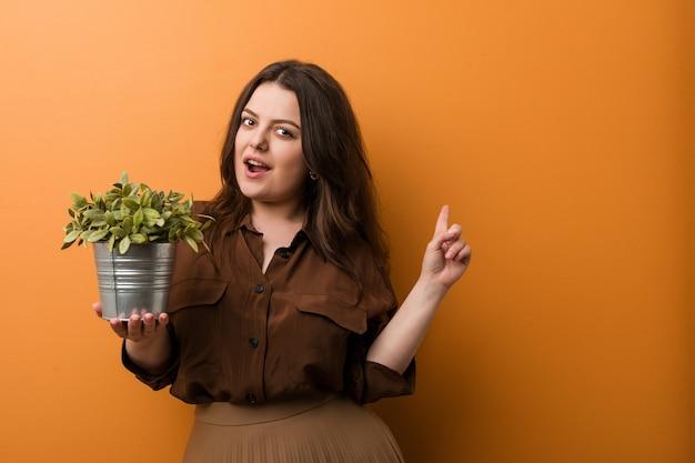 Młoda kobieta krzywego plus size trzyma roślinę, uśmiechając się radośnie, wskazując palcem wskazującym z dala.