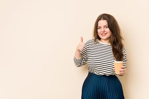 Młoda kobieta krzywego trzymając kawę, uśmiechając się i podnosząc kciuk do góry