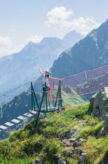 Młoda kobieta krzyżuje otchłań na linowym moscie, sochi, rosja