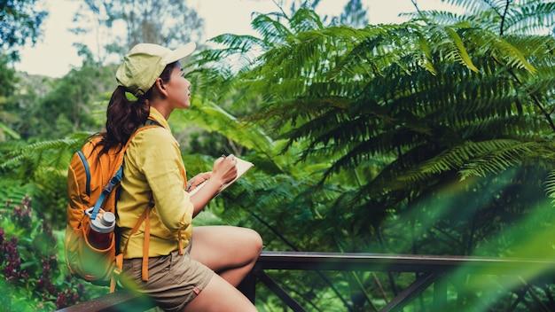 Młoda kobieta, która siedzi, pisze, nagrywa i studiuje naturę lasu.