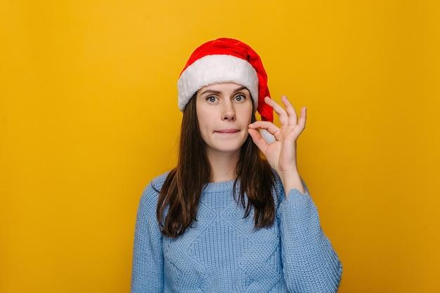 Młoda kobieta, która traci usta gestem zamka błyskawicznego jako obietnicy zachowania tajemnicy, ubrana w świąteczną czapkę i zimowy sweter, odizolowana na pastelowym żółtym tle studia. koncepcja szczęśliwego nowego roku