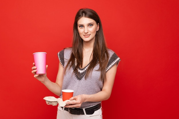 Młoda kobieta, która trzyma kawę na wynos