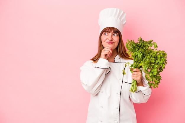 Młoda kobieta kucharz kaukaski gospodarstwa pietruszka na białym tle na różowym tle patrząc w bok z wyrazem wątpliwości i sceptyczny.