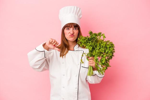 Młoda kobieta kucharz kaukaski gospodarstwa pietruszka na białym tle na różowym tle pokazując gest niechęci, kciuk w dół. koncepcja niezgody.
