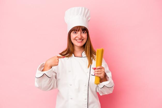 Młoda kobieta kucharz kaukaski trzyma makaron na białym tle na różowym tle osoba wskazująca ręcznie na miejsce na koszulkę, dumna i pewna siebie