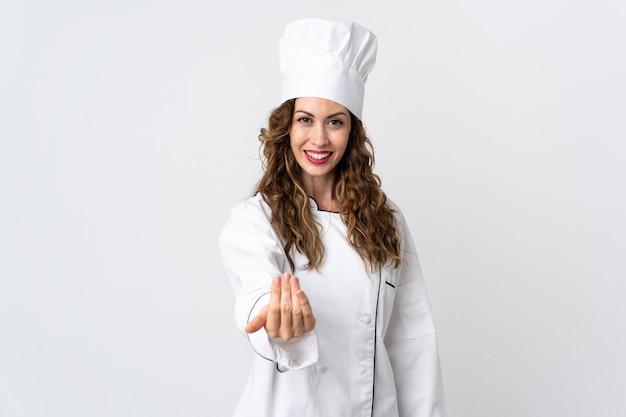 Młoda kobieta kucharz na białym tle na białej ścianie zaprasza do przyjścia z ręką.