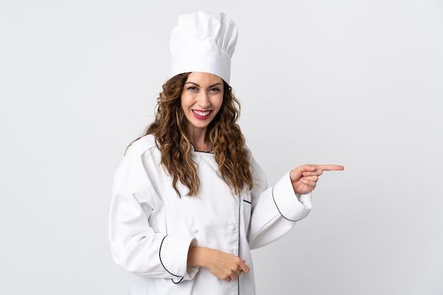 Młoda kobieta kucharz na białym tle na białym tle wskazując palcem w bok