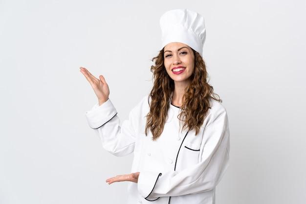 Młoda kobieta kucharz na białym tle wyciągając ręce na bok za zaproszenie do przyjazdu
