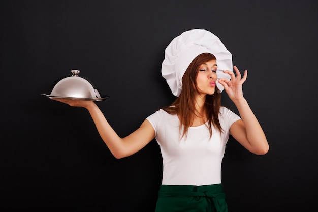Młoda kobieta kucharz poleca danie główne